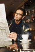 Man reading newspaper at cafe