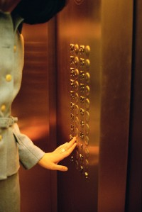 Businesswoman Pushing Elevator Button